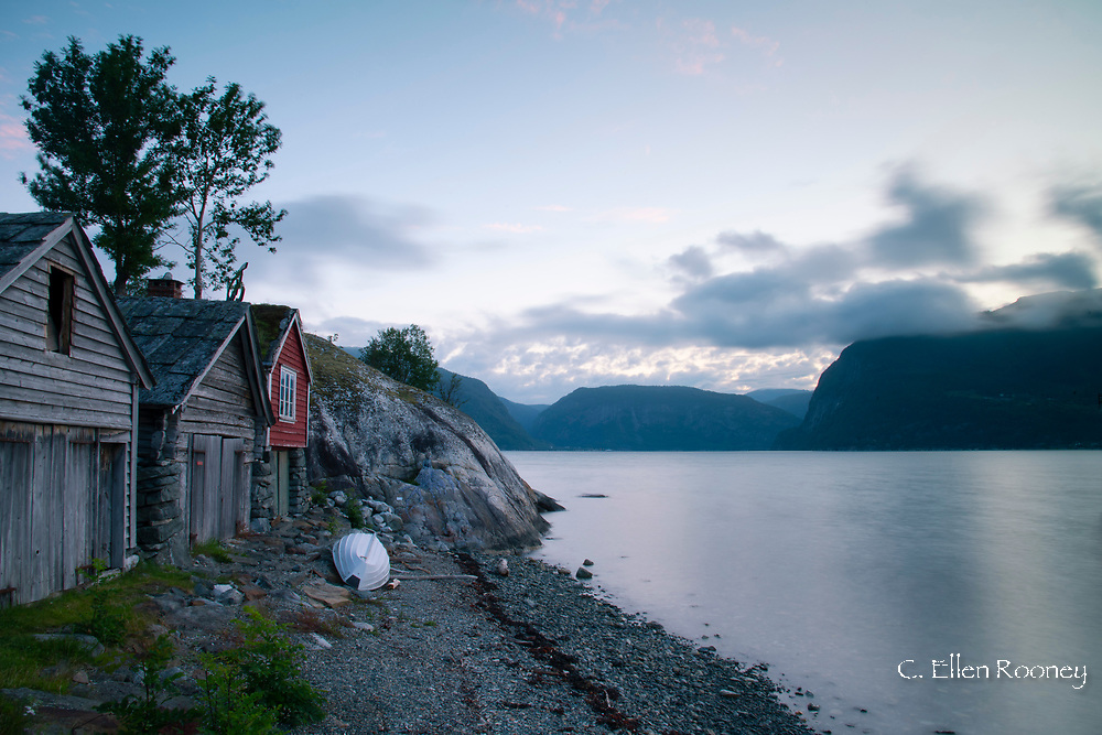 Old wooden buildings along the coast of Hardanger Fjord near Utne, Vestlandet, Norway, Europe