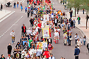 "03 DECEMBER 2011 - PHOENIX, AZ:  A procession to honor the Virgin of Guadalupe in downtown Phoenix Saturday. The Phoenix diocese of the Roman Catholic Church held its Sixth Annual Honor Your Mother Day Saturday to honor the Virgin of Guadalupe. According to Mexican Catholic tradition, on December 9, 1531 Juan Diego, an indigenous peasant, had a vision of a young woman while he was on a hill in the Tepeyac desert, near Mexico City. The woman told him to build a church exactly on the spot where they were standing. He told the local bishop, who asked for some proof. He went back and had the vision again. He told the lady that the bishop wanted proof, and she said ""Bring the roses behind you."" Turning to look, he found a rose bush growing behind him. He cut the roses, placed them in his poncho and returned to the bishop, saying he had brought proof. When he opened his poncho, instead of roses, there was an image of the young lady in the vision. The Virgin is now honored on Dec 12 in Catholic churches throughout Latin America and in Hispanic communitied in the US.     PHOTO BY JACK KURTZ"