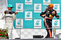 SEPANG, Oct. 1, 2017  Mercedes driver Lewis Hamilton (L) of Britain pours champagne on Red Bull driver Max Verstappen on the podium after the Formula One Malaysia Grand Prix at the Sepang Circuit in Malaysia, on Oct. 1, 2017. Max Verstappen claimed the title of the event. (Credit Image: © Chong Voon Chung/Xinhua via ZUMA Wire)
