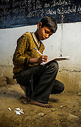 26th March 2014, Shakarpur, New Delhi, India. Govind Mauyra (12) copies from a blackboard at a makeshift school under a metro bridge near the Yamuna Bank Metro station in Shakarpur, New Delhi, India on the 26th March 2014<br /> <br /> Rajesh Kumar Sharma (born 01/02/1970), started this makeshift school in 2011. Six mornings a week he teaches underprivileged children for three hours while his younger brother replaces him at his general store in Shakarpur. His students are children of labourers, rickshaw-pullers and farm workers. This is the 3rd site he has used to teach under privileged children in the city, he began in 1997. <br /> <br /> PHOTOGRAPH BY AND COPYRIGHT OF SIMON DE TREY-WHITE<br /> + 91 98103 99809<br /> email: simon@simondetreywhite.com<br /> photographer in delhi<br /> journalist