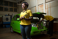"""Pauline Korukundo, 29, Vehicle Integration Manager at Kiira Motors Corporation, with Uganda's first electric vehicle-- the Kiira EV-- at the workshop where it was created at Makerere University, in Kampala, Uganda. """"My vision for the company is to see cars made by us, so that we as Ugandans can begin to believe more in ourselves,"""" says Korukundo."""