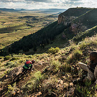 A boy looks on as Kevin Landry rides towards Roma, Lesotho, Africa.
