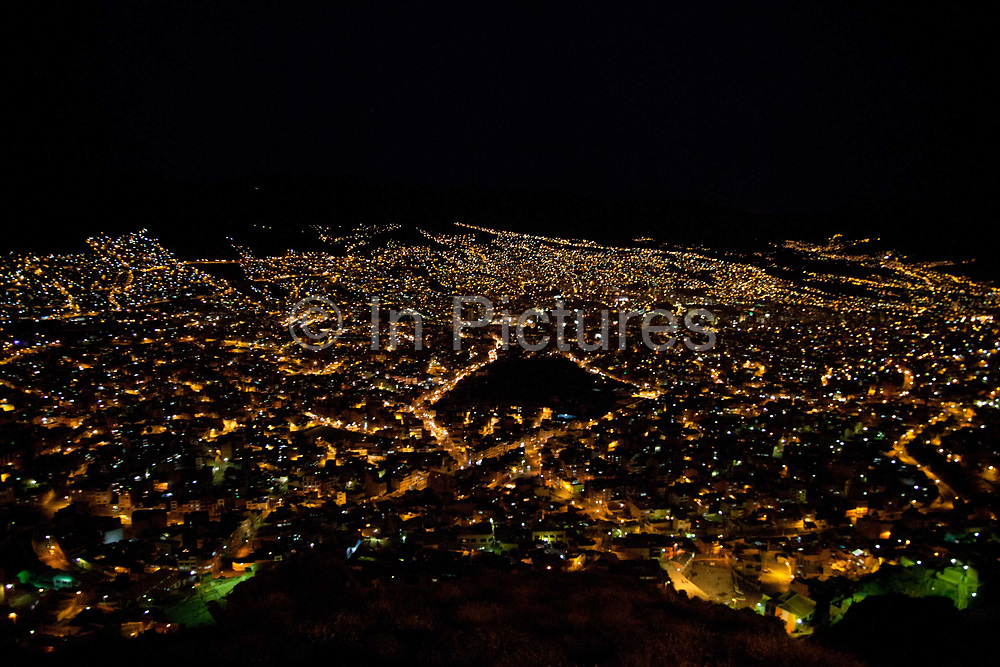 Overhead view cityscape of La Paz at night, streetlights and valleys visible.