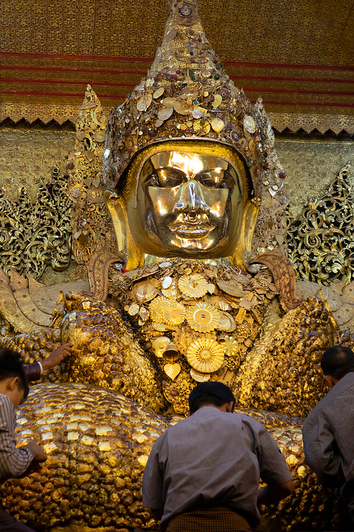 Pilgrims applying gold leaf to the Mahamuni Buddha (literal meaning: The Great Sage) It is a Buddhist temple and major pilgrimage site, located southwest of Mandalay