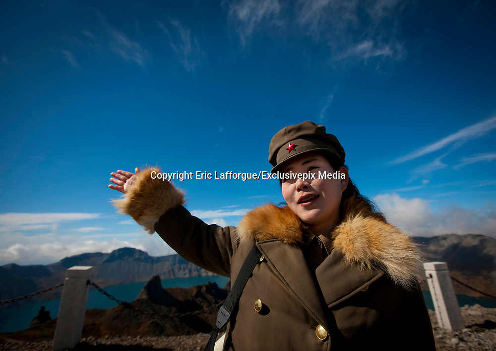 """PAEKTU, LAND OF NORTH KOREAN LEGENDS<br /> <br /> Mount Paektu volcano is considered a holy place for North Koreans. It is deemed the place of origin for them. The country's founding father Kim Il- Sung commanded anti-Japanese guerrilla in the 50's from a secret camp in this place.<br /> North Korea says his son Kim Jong-il was born there in 1942. He was actually born in Siberia, where his father had taken refuge from Japanese troops.<br /> The dear Leaders are said to have a """"mount Paektu bloodline ». A famous slogan says: « Let us all turn out in the general offensive to hasten final victory in the revolutionary spirit of Paektu! »<br /> A new probelm may erupt: when North Korea tests a nuclear weapon, specialists say the energy could trigger a volcanic...eruption in Paektu. That could be a huge disaster, killing thousands in North Korea and on the chinese side too.<br /> <br /> Photo shows:  The summit reaches 2,744 meters high. The local guide, wrapped up in his dog hair coat, narrates the exploits of the country's founder. Winter lasts 8 months. She told the lowest temperature she had to afford was -36°!<br /> ©Eric Lafforgue/Exclusivepix Media"""