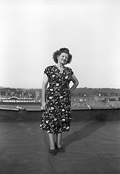 Woman in a dress standing on a NYC rooftop