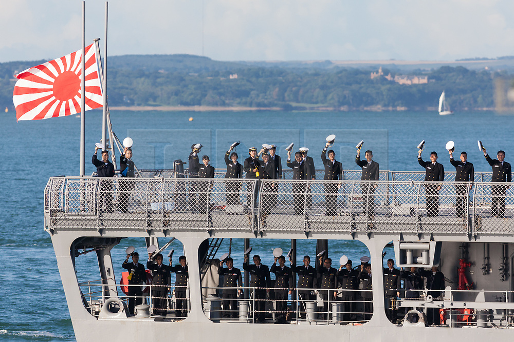 © Licensed to London News Pictures. 25/08/2018. Portsmouth, UK.  Crew waving their hats aboard the 143-metre long cadet training vessel JS Kashima (3508) from the Japanese Maritime Self Defense Force (JMSDF) arriving in Portsmouth this morning, 25th August 2018.  This vessel and the 151-metre long destroyer JS Makinami (112) have recently conducted a passing exercise (PASSEX) with Standing NATO Maritime Group One (SNMG1) in the Baltic Sea. The ships will moor alongside in Portsmouth Naval Base and be opened to visitors over the bank holiday weekend until 28th August 2018. Photo credit: Rob Arnold/LNP