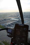 Nederland, Haarlemmermeer, Schiphol, 15-02-2007;  Schiphol airport, zicht op stationsgebouw (terminal) van de luchthaven met verkeerstoren, verschillende van de pieren met 'slurfen' ( voor in- en uittappen passagiers) zijn tevens in beeld; ook in beeld het instumentarium van de Hughes 300 C (GPS, hoogtemeter); helikopter; helicopter, cockpit, vliegverkeer, vliegen, verkeersleiding, infrastuctuur, verkeer en vervoer, start, landing.luchtfoto (toeslag); aerial photo (additional fee required); .foto Siebe Swart / photo Siebe Swart