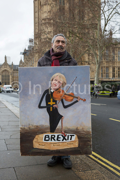 Political satire artist Kaya Mar poses with his artwork of Prime Minister Theresa May playing the violin with one foot on a coffin titled Brexit on the 16th January 2019 in London in the United Kingdom. Prime Minister Theresa May is expected to win a confidence vote on the 16th, despite a crushing defeat over her Brexit deal.
