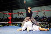 Female wrestler showing victory sign whilst holding down her opponents including the referee. Lucha Libre wrestling origniated in Mexico, but is popular in other latin Amercian countries, including in La Paz / El Alto, Bolivia. Male and female fighters participate in the theatrical staged fights to an adoring crowd of locals and foreigners alike.
