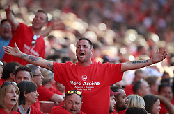 An Arsenal fan wearing a Merci Arsene t-shirt in the stands