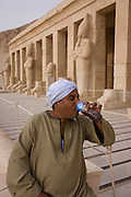 "A local guide sips water near the colossi of Pharaohs at the ancient Egyptian Temple of Hatshepsut near the Valley of the Kings, Luxor, Nile Valley, Egypt. The Mortuary Temple of Queen Hatshepsut, the Djeser-Djeseru, is located beneath cliffs at Deir el Bahari (""the Northern Monastery""). The mortuary temple is dedicated to the sun god Amon-Ra and is considered one of the ""incomparable monuments of ancient Egypt."" The temple was the site of the massacre of 62 people, mostly tourists, by Islamists on 17 November 1997."