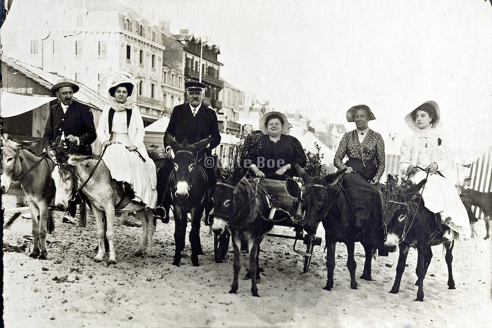 adults sitting on donkeys while vacation on the beach resort early 1900s