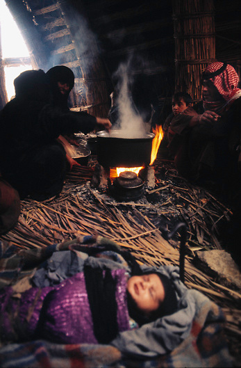 Baby sleeps in kitchen of Marsh Arab reed house on a small island in village in the wetlands of Southern Iraq while women of the family stir cooking pots