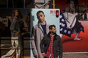 Waiting man in front of H&M menswear poster outside central London shop.
