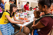 20 MAY 2013 - MAE KASA, TAK, THAILAND:  A Burmese pharmacy worker talks to a patient about the medications she is receiving at the SMRU clinic in Mae Kasa, Thailand. Health professionals are seeing increasing evidence of malaria resistant to artemisinin coming out of the jungles of Southeast Asia. Artemisinin has been the first choice for battling malaria in Southeast Asia for 20 years. In recent years though,  health care workers in Cambodia and Myanmar (Burma) are seeing signs that the malaria parasite is becoming resistant to artemisinin. Scientists who study malaria are concerned that history could repeat itself because chloroquine, an effective malaria treatment until the 1990s, first lost its effectiveness in Cambodia and Burma before spreading to Africa, which led to a spike in deaths there. Doctors at the Shaklo Malaria Research Unit (SMRU), which studies malaria along the Thai Burma border, are worried that artemisinin resistance is growing at a rapid pace. Dr. Aung Pyae Phyo, a Burmese physician at a SMRU clinic just a few meters from the Burmese border, said that in 2009, 90 percent of patients were cured with artemisinin, but in 2010, it dropped to about 70 percent and is now between 55 and 60 percent. He said the concern is that as it becomes more difficult to clear the parasite from a patient, progress that has been made in combating malaria will be lost and the disease could make a comeback in Southeast Asia.    PHOTO BY JACK KURTZ