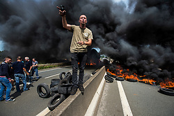 © London News Pictures. Calais, France. A disgruntled french ferry port worker gestures to English media to go away, during a demonstration in which tyres were burt on the main road leading to the Calais Ferry port.  Migrants attempting to reach the UK via the Eurotunnel at Calais in France. The situation has reached crisis point, which French police over run by attempts to cross the border. Photo credit: Ben Cawthra /LNP