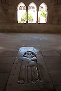 Worn smooth after centuries of passing feet, a 17th century tomb in the floor of the Cloister Of Alcobaca Monastery, Portugal.