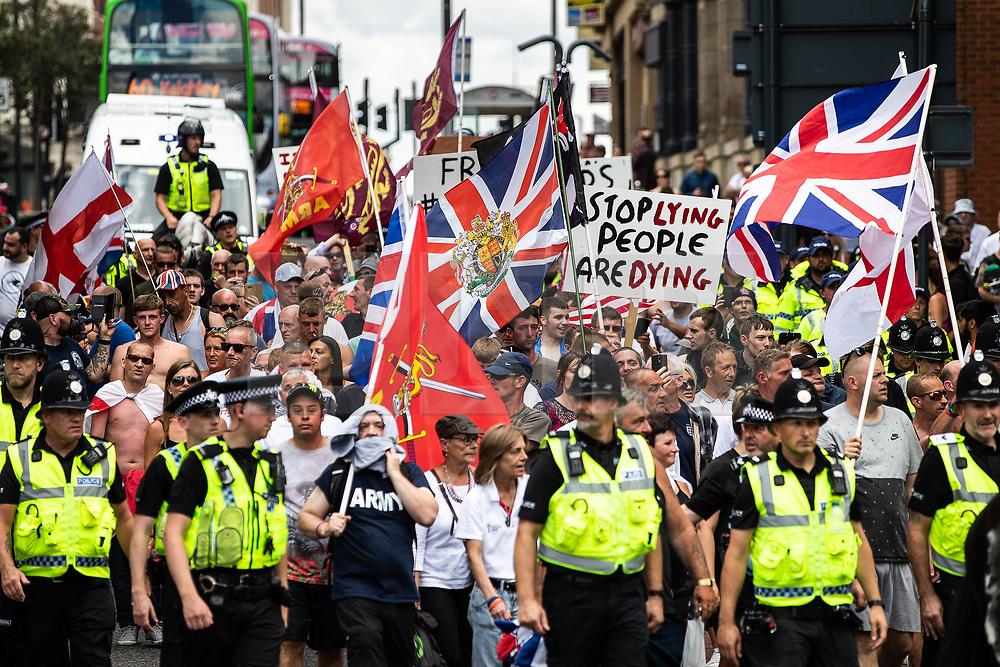 "© Licensed to London News Pictures . 07/07/2018 . Leeds , UK . An anti-Islam demonstration by supporters of jailed EDL founder Tommy Robinson , including those from the "" Yorkshire Patriots "" and "" First for Britain "" , in Leeds City Centre , opposed by anti-fascists . Robinson ( real name Stephen Yaxley-Lennon ) was convicted of Contempt of Court in May 2018 after committing a second offence , whilst serving a suspended sentence for the same crime . Photo credit : Joel Goodman/LNP"
