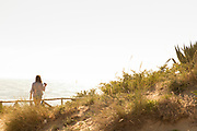 Rear view of tourist looking at sea, Cadiz, Andalusia, Spain