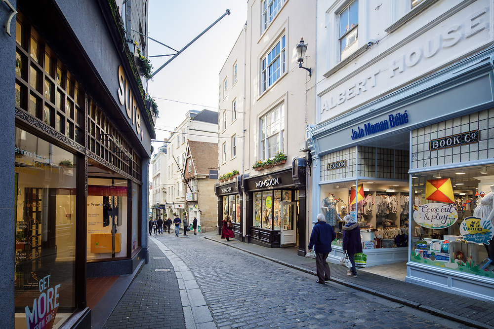 Shoppers walking past retail shops and clothing stores on pedestrianised streets in the centre of town in St Peter Port, Gunersey, Channel Islands