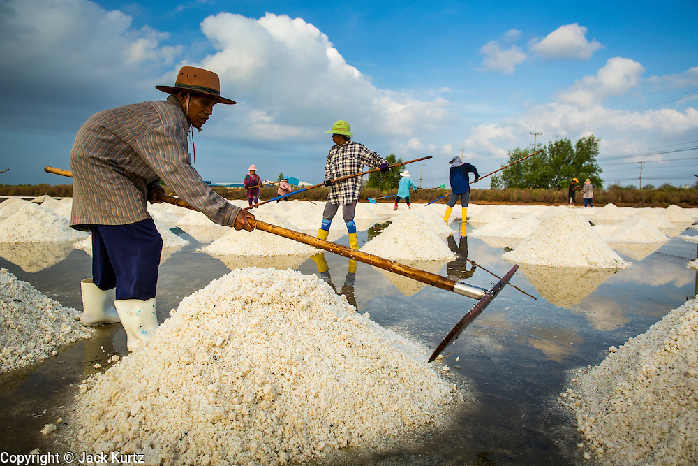 24 APRIL 2013 - SAMUT SONGKHRAM, SAMUT SONGKHRAM, THAILAND:  Workers in a salt field in Samut Songkhram pile salt so it can be harvested. The 2013 salt harvest in Thailand and Cambodia has been impacted by unseasonably heavy rains. Normally, the salt fields are prepped for in December, January and February, when they're leveled and flooded with sea water. Salt is harvested from the fields from late February through May, as the water evaporates leaving salt behind. This year rains in December and January limited access to the fields and rain again in March and April has reduced the amount of salt available in the fields. Thai salt farmers are finishing the harvest as best they can, but the harvest in neighboring Cambodia ended 6 weeks early because of rain. Salt has traditionally been harvested in tidal basins along the coast southwest of Bangkok but industrial development in the area has reduced the amount of land available for commercial salt production and now salt is mainly harvested in a small part of Samut Songkhram province.     PHOTO BY JACK KURTZ