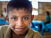 06 NOVEMBER 2014 - SITTWE, RAKHINE, MYANMAR: A boy in a school for Rohingya IDPs in the classroom. After sectarian violence devastated Rohingya communities and left hundreds of Rohingya dead in 2012, the government of Myanmar forced more than 140,000 Rohingya Muslims who used to live in and around Sittwe, Myanmar, into squalid Internal Displaced Persons camps. The government says the Rohingya are not Burmese citizens, that they are illegal immigrants from Bangladesh. The Bangladesh government says the Rohingya are Burmese and the Rohingya insist that they have lived in Burma for generations. The camps are about 20 minutes from Sittwe but the Rohingya who live in the camps are not allowed to leave without government permission. They are not allowed to work outside the camps, they are not allowed to go to Sittwe to use the hospital, go to school or do business. The camps have no electricity. Water is delivered through community wells. There are small schools funded by NOGs in the camps and a few private clinics but medical care is costly and not reliable.   PHOTO BY JACK KURTZ