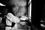 A monk working in the kitchen at Sancta Maria Abbey at Nunraw, East Lothian, home since 1946 to the Order of Cistercians of the Strict Observance. Around 15 monks were resident at Nunraw in 1996, undertaking a mixture of daily tasks and strict religious observance. The present purpose-built building dates from 1969 when the monks moved from the nearby Nunraw house.