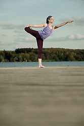 Woman practicing yoga on jetty, Woerthsee, Bavaria, Germany