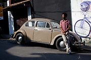 Actor Bruno Barbosa in front of an old beetle car in the street in Vidigal. Since pacification in 2011, Vidigal has slowly become known as what some call a model favela, seen as the safest favela in Rio, home to a mixed community which now includes foreigners, hostels, restaurants, theatres and creative businesses.