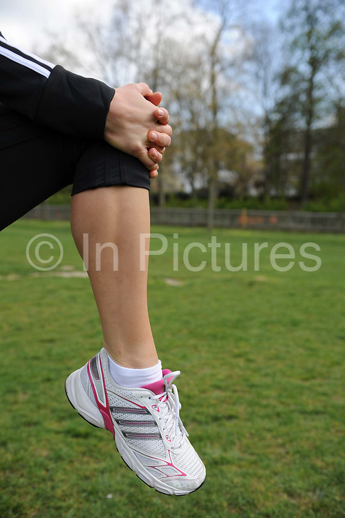 A woman exercising in a park in London, UK. Fitness, exercise and wellbeing has never been more popular in the United Kingdom as people strive to live healthy lives.