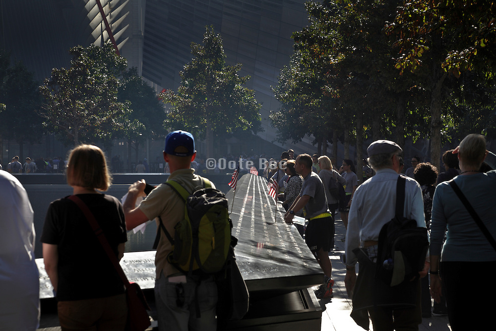 early morning people at the South Pool of the 9/11 memorial to the World Trade Center in New York City