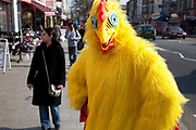 Man dressed as a chicken to promote his restaurant in Southall in West London, also known as 'Little India' by some, is an area almost completely populated by people from South Asia. Figures show that the area is approximately 50 percent Indian in origin although walking the streets it would appear far higher as the local people go about their shopping in the many shops specialising in goods specific to this culture. The mix of religions is mainly Sikh, Hindu and Muslim.<br /> <br /> Southall is primarily a South Asian residential district. 1950 was when the first group of South Asians arrived in Southall, reputedly recruited to work in a local factory owned by a former British Indian Army officer. This South Asian population grew due to the closeness of expanding employment opportunities. The most significant cultural group to settle in Southall are Indian Punjabis.