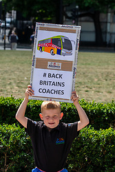 © Licensed to London News Pictures. 20/07/2020. London, UK. Harry Scott 6 from Manchester holds a placard during a coach demonstration in Parliament Square. The demonstration by 500 coaches took place in Westminster including driving around Parliament Square asking government for more help for the coach industry. Last week, Prime Minister Boris Johnson urged Britons to return back to working in offices to help service industries and the economic recovery. Photo credit: Alex Lentati/LNP