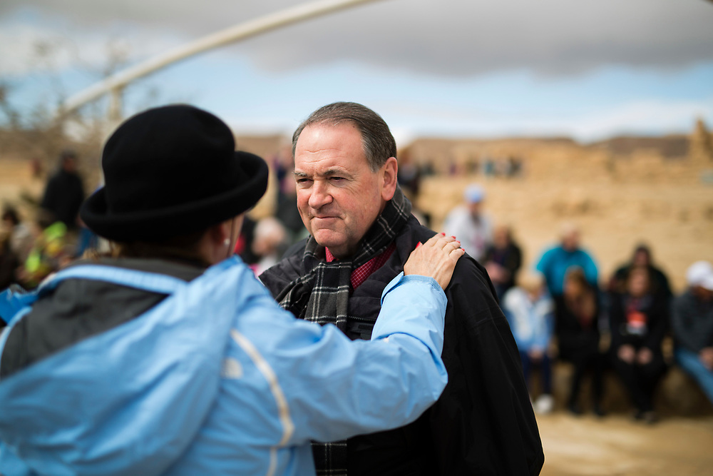 Former Arkansas governor Mike Huckabee is seen as he talks with an American Evangelical Christian tourist, part of a group led by him, during a visit to the ancient hilltop fortress of Masada in the Judean desert in Israel, on February 19, 2015. The ancient ruined desert fortress on a wind-swept plateau overlooking the Dead Sea is seen by many as an emblem of Israel's fighting spirit, it is believed to be the place where close to a thousand Jewish rebels killed themselves and each other about two millennia ago, rather than surrender and fall into slavery under the Romans.