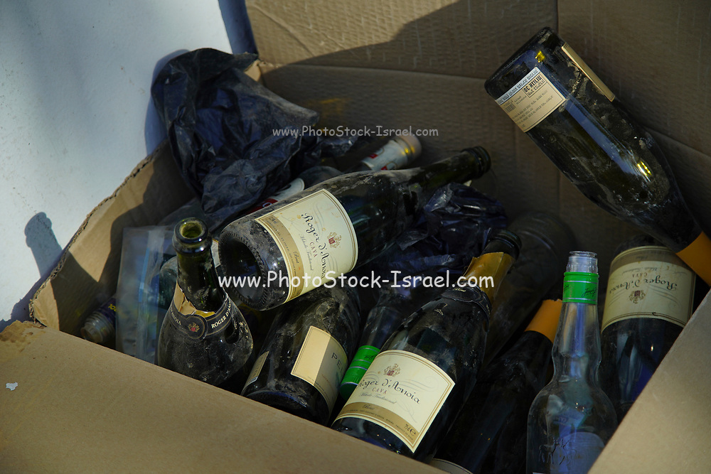 A stack of used wine bottles waiting to be taken to a recycling bin