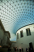 A modern, highly architectural glass lattice roof covers the entire area of the Great Court of the British Museum in London, UK.