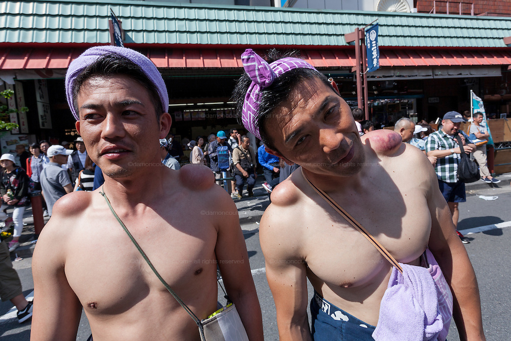 Portrait of festival supporters showing off the large lump they have on their shoulders from carrying Mikoshi around the streets of Asakusa during the Sanja matsuri. Asakusa, Tokyo, Japan. Sunday May 15th 2016 The Sanja matsuri is one of the biggest festivals in Japan. Taking place over the 3 days of the second weekend of May (May 13th to 15th) it features many mikoshi, or portable shrines, that are carried around by local groups to bring blessings and prosperity to their neighbourhoods