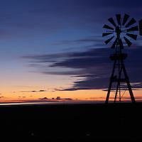 Canada, Saskatchewan, Tompkins, Windmill along lights of Trans-Canada Highway on autumn evening