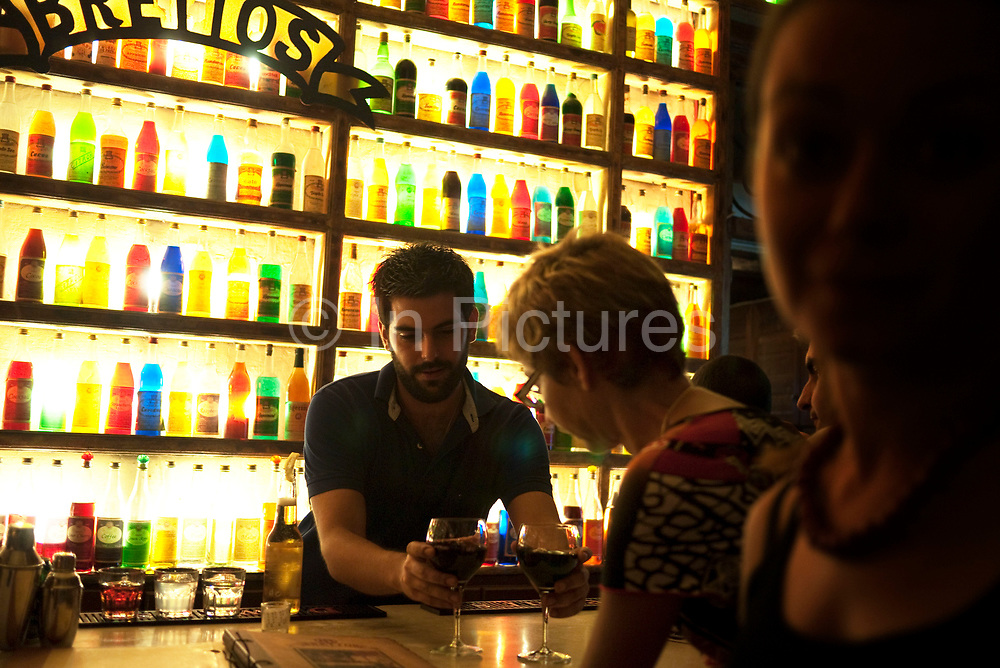 """Patrons having drinks at Bretton bar in Athens. The unsuspected visitor of the historic center of Athens cannot miss the hundreds of colorful bottles and lights that decorate the walls of """"Brettos"""".  """"BRETTOS"""" is the oldest distillery in Athens. It started operating for the first time back in 1909 at the ground level of an Athenian old mansion in the heart of Plaka. At those premises, his founder, Michael Brettos, started producing ouzo, brandy and few liqueur flavours. It is the 2nd oldest distillery in Europe. Athens is the capital and largest city of Greece. It dominates the Attica periphery and is one of the world's oldest cities, as its recorded history spans around 3,400 years. Classical Athens was a powerful city-state. A centre for the arts, learning and philosophy."""