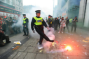 A policeman moves a flare in Oxford Street during a protest organised by the Trades Union Congress (TUC), called 'The March for the Alternative,' in central London. Tens of thousands of Britons protested against the coalition government's austerity measures on Saturday in the biggest demonstration in the capital since 2003.