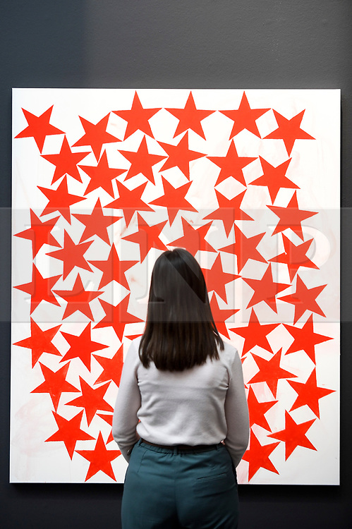 """© Licensed to London News Pictures. 21/06/2019. LONDON, UK. A staff member next to """"Cluster"""", 2015, by Charline von Heyl (Est. GBP 50-70k) at the preview of a Contemporary Art auction at Sotheby's New Bond Street.  The sales take place 26 and 27 June 2019.  Photo credit: Stephen Chung/LNP"""