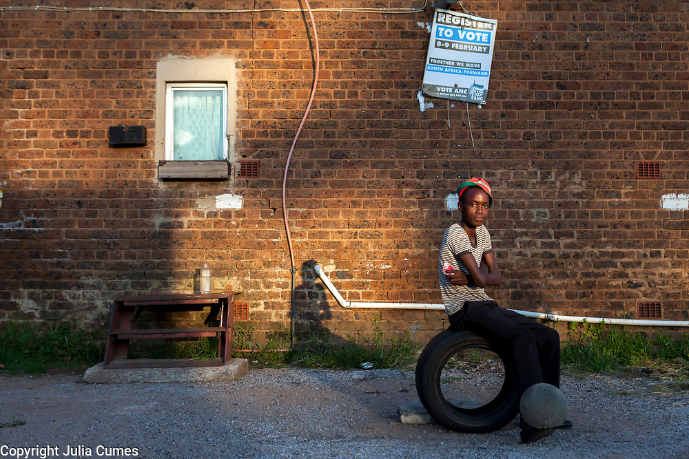 A teenaged boy sits on a tire and bounces a soccer ball on his feet at one of Durban Deep's old hostels on the outskirts of Johannesburg, South Africa. Behind him a poster pro-ANC poster encourages residents to register to vote.