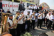 """King Dorian Cioaba of the Roma Gypsies with the funeral banad awaits the arrival of the coffin of his father, the late king. The route from Florin Cioba's home to the cemetery - there are crowds of people. Many people, onlookers Gypsy and not line the streets, watching from windows and the pavement. The hearse is surrounded by security.<br /><br />Florin Ciaoba's funeral and the crowning of two kings. Daniel and Dorian were crowned, Danile with the bigger crown is King of Romanian Roma Gypies whilst his older Brother Dorian has the smaller crown and is King of Gypsies of the world and deals with foriegn affairs. His hearse (a lorry) packed with security guards is taken from The Cioaba family home to the cemetery<br /><br />Florin Tănase Cioabă (1954 – 18 August 2013) was a Romanian Romani Pentecostal minister and self-proclaimed """"King of Roma around the world"""". He died on 18 August 2013 of cardiac arrest at Akdeniz Üniversitesi in Antalya. He was 58 years old.<br /><br />In September 2003, Florin Cioaba sparked controversy when he married his 12 year-old daughter Ana-Maria to Mihai Bitrita, a Roma boy aged 15. However, following the wave of criticism, he promised to work to uproot the tradition of child marriages among the Roma. Florin Cioaba also encouraged Roma families to send their children to school during his attempt to fight poverty resulting from a lack of education.<br /><br />Cioaba was elected president of the International Romani Union in April this year"""