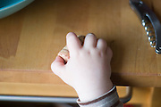 A childrens hand takes something from a table