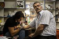 Un pellegrino siriano in visita a Gerusalemme si fa tatuare un simbolo religioso sull'avambraccio come ricordo del viaggio