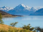 The peak of Aoraki / Mount Cook rises to 3755 meters / 12,349 feet elevation by Lake Pukaki in Aoraki / Mount Cook National Park, South Island, New Zealand. In 1990, UNESCO honored Te Wahipounamu - South West New Zealand as a World Heritage Area.