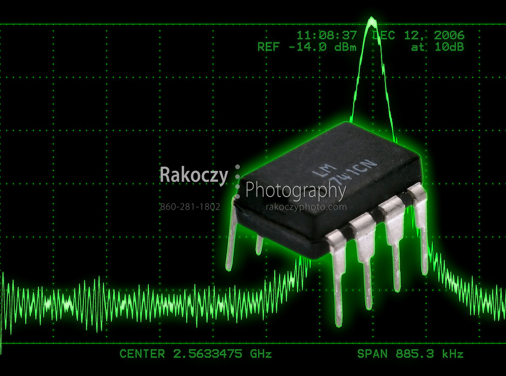A small op-amp integrated circuit set against an illustration depicting a occiliscope display of a signal peak.