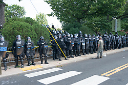 August 12, 2017 - Charlottesville, Virginia, United States - Police stand on sidewalk as Neo-Nazis, white supremacists and other alt-right factions scuffled with counter-demonstrators near Emancipation Park, formerly 'Lee Park' in downtown Charlottesville. After fighting between factions escalated, Virginia State Police ordered the evacuation by all parties and cancellation of the 'Unite The Right' rally scheduled to take place in the park. (Credit Image: © Albin Lohr-Jones/Pacific Press via ZUMA Wire)