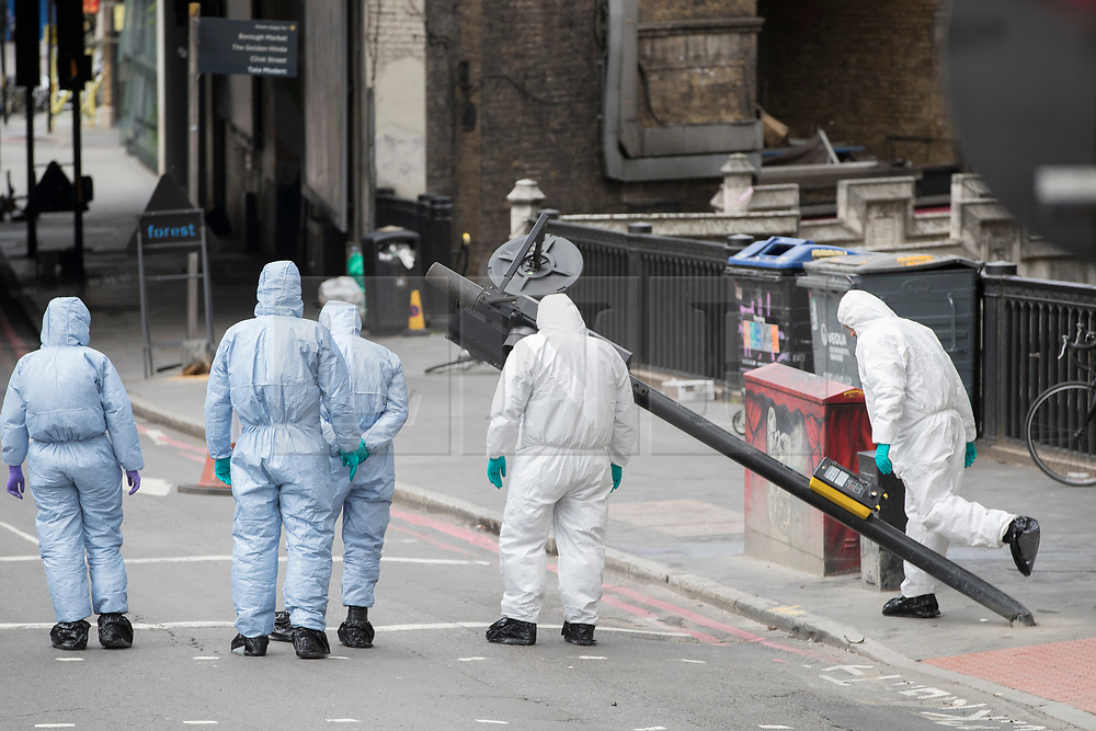 © Licensed to London News Pictures. 05/06/2017. London, UK.  Police forensic officers examine the area where a van crashed on London Bridge during a terrorist attack on Saturday evening. Three men attacked members of the public  after a white van rammed pedestrians on London Bridge.   Ten people including the three suspected attackers were killed and 48 injured in the attack. Photo credit: Peter Macdiarmid/LNP